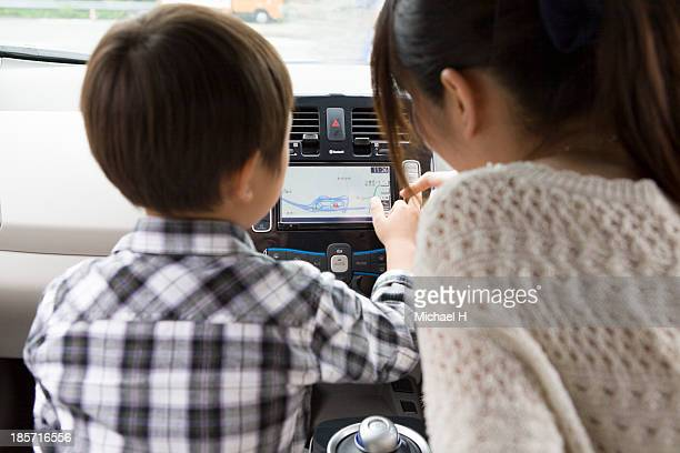 mother and child in electric car pointing at gps - family inside car stock photos and pictures