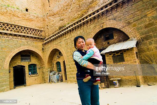 Mother and child in front of typical house.