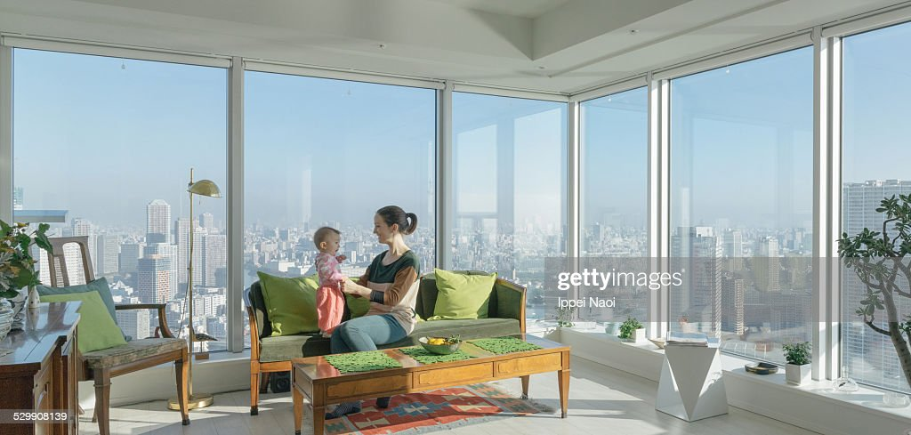 Mother and child in high rise apartment with view : ストックフォト