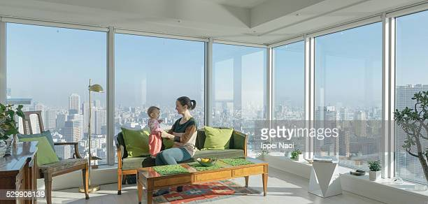 Mother and child in high rise apartment with view