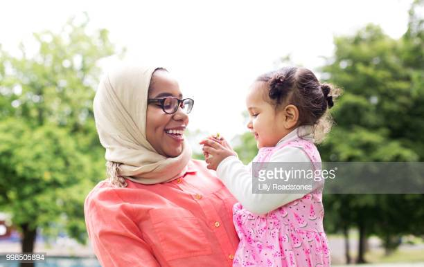 Mother and child laughing together outside in public park
