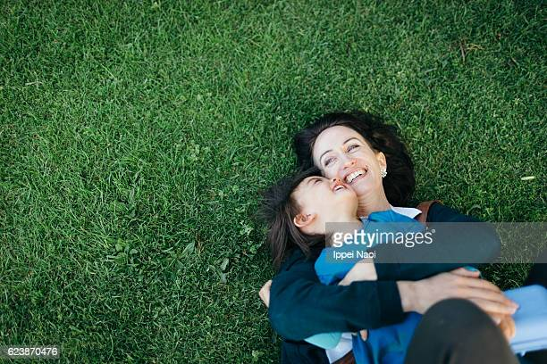 Mother and child lying on grass and cuddling