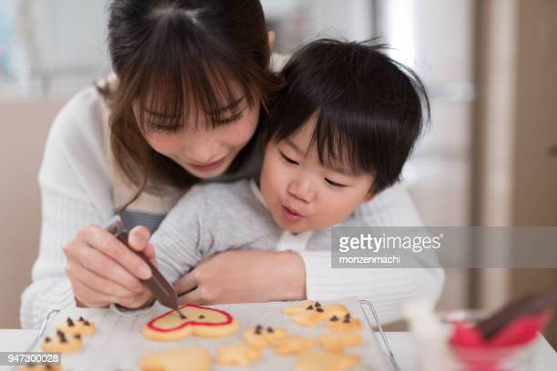 Mother and child making cookie together in kitchen