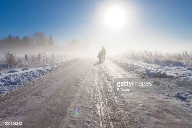 mother and child on foggy snow road near farm - gennaio foto e immagini stock