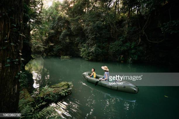 Mother and child on inflatable boat having adventure through forest river, Japan