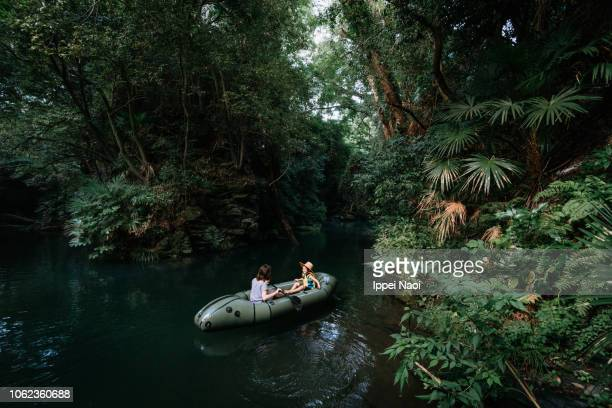 Mother and child on inflatable boat on river in lush forest, Japan