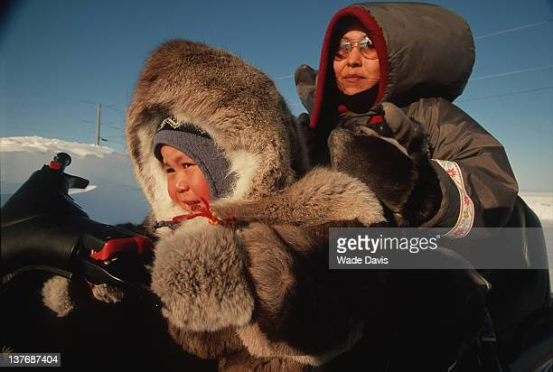 Mother and child on snow mobile Igloolik Nunavut Canada 2006
