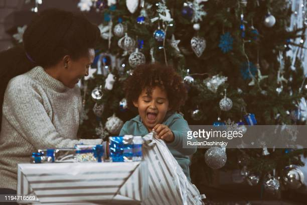 mother and child opening christmas presents. - 2 5 months stock pictures, royalty-free photos & images