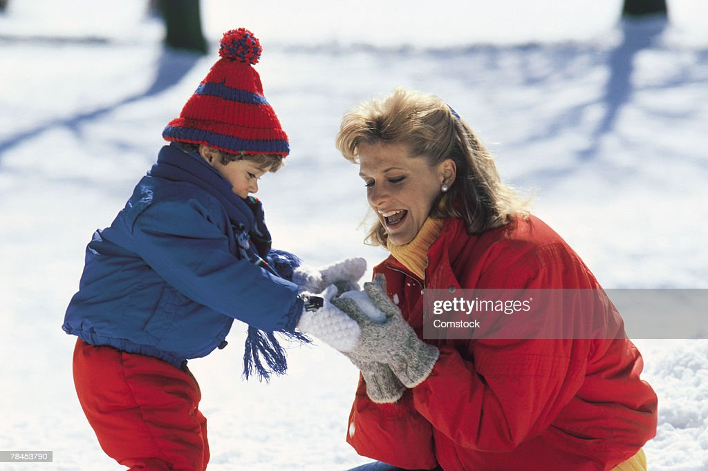 Mother and child outdoors making a snowball : Stockfoto