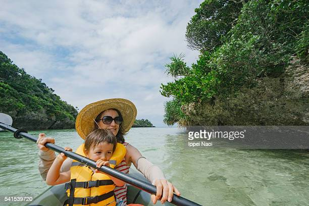 Mother and child paddling a kayak together in tropical lagoon