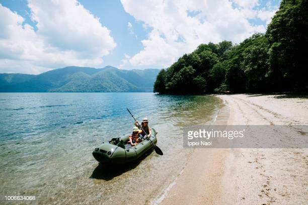 mother and child paddling inflatable raft along beach, lake chuzenji, nikko, japan - lakeshore stock pictures, royalty-free photos & images