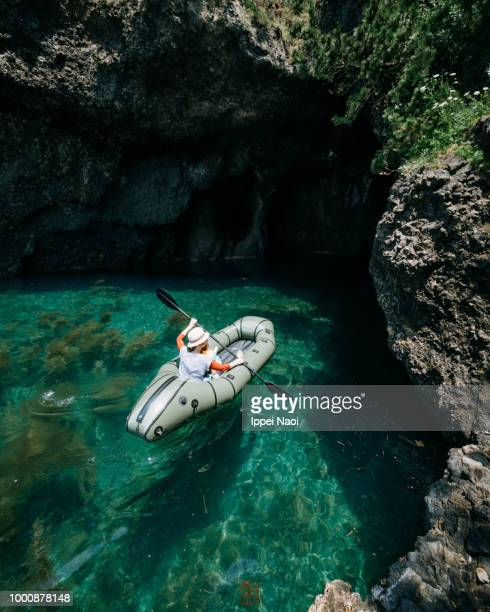 Mother and child paddling packraft boat into sea cave, Japan