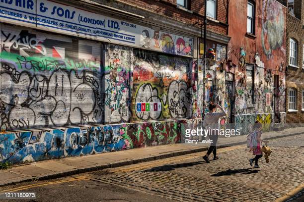 Mother and child passing a boarded up shop covered in graffitti on a wall in Brick Lane during the coronavirus pandemic on the 24th April 2020 in...