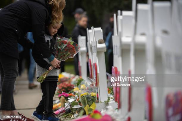 A mother and child place flowers at a memorial for victims of the mass shooting that killed 11 people and wounded 6 at the Tree Of Life Synagogue on...