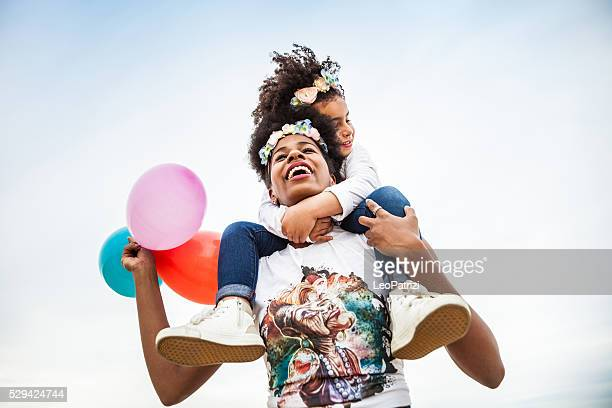 mother and child play together celebrating - birthday balloons stock photos and pictures