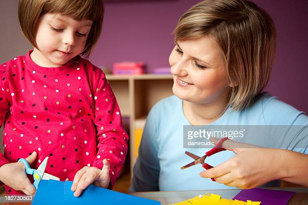 Mother and child play with scissors and construction paper