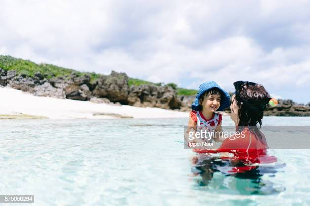 mother and child playing in clear tropical water, amami islands, japan - 鹿児島県 ストックフォトと画像