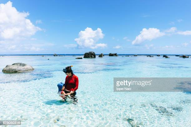 Mother and child playing in coral lagoon, Amami Islands, Japan