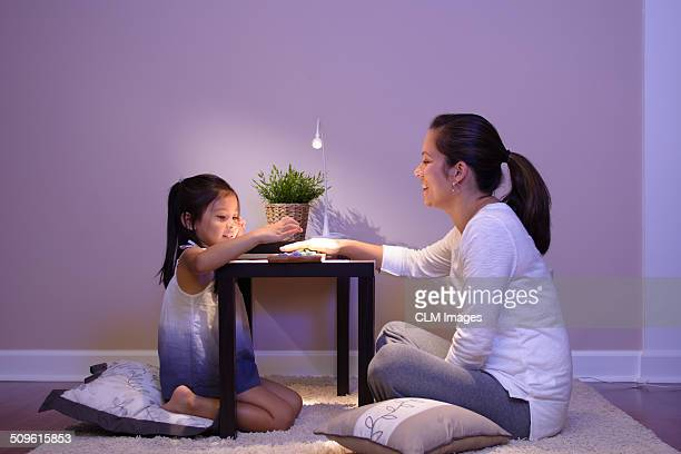 Mother and child playing Mancala.