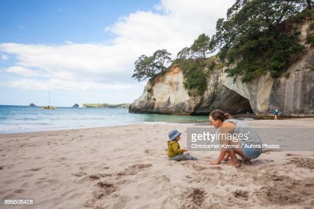 Mother and child playing on beach, Hahei, Coromandel, New Zealand