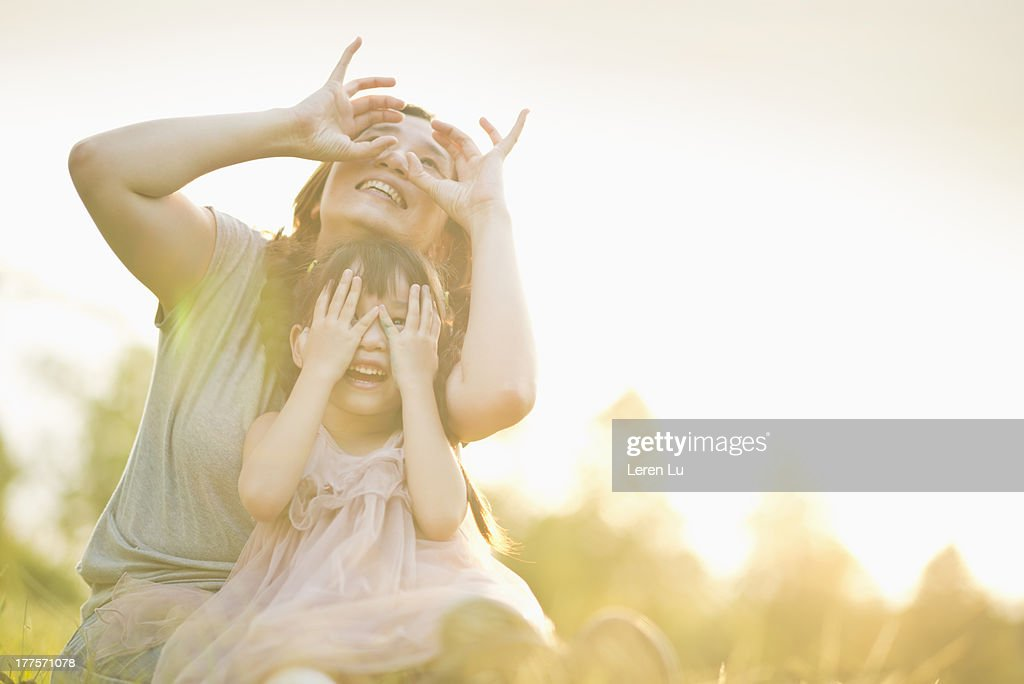 Mother and child playing under sunset : Stock Photo