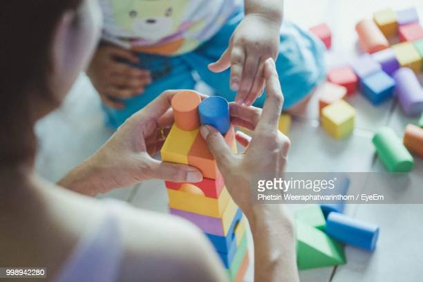 mother and child playing with blocks at home - block shape stock pictures, royalty-free photos & images
