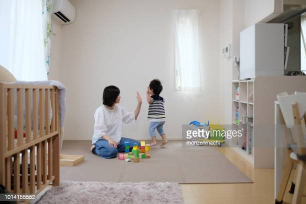 mother and child playing with building blocks in authentic house - tidy room stock pictures, royalty-free photos & images