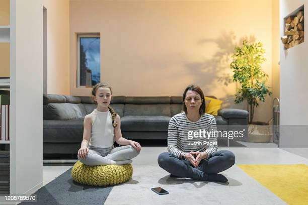 mother and child practising meditation in living room - mental wellbeing stock pictures, royalty-free photos & images