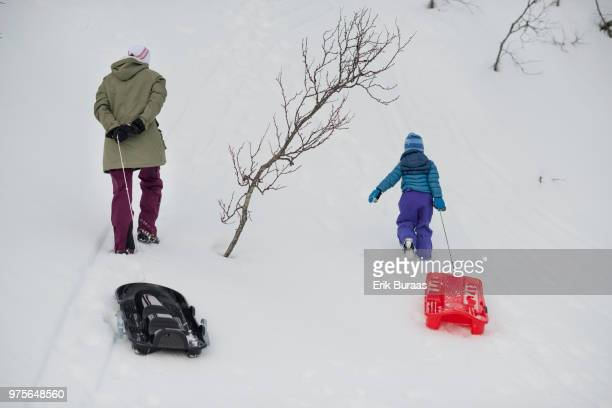 Mother and child pulling a sledge each