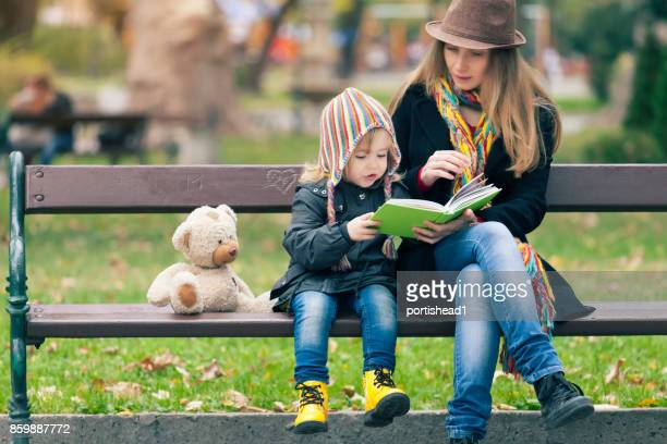 mother and child reading a book in park - one parent stock pictures, royalty-free photos & images