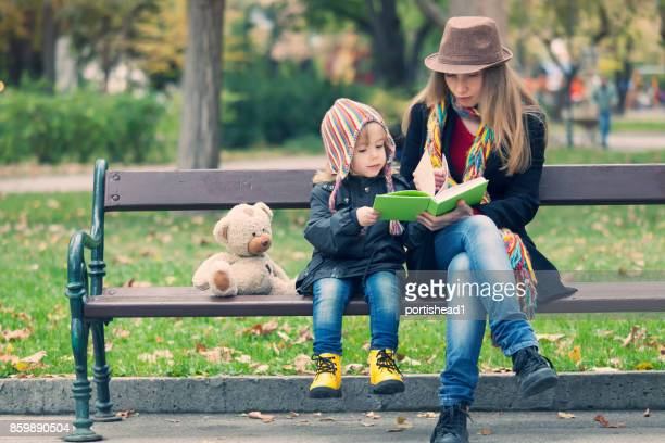 Mother and child reading a book in park