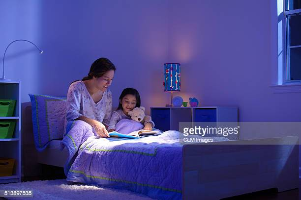 Mother and child reading before bedtime.