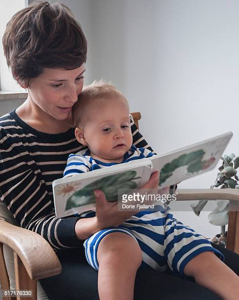 mother and child reading in a book - dorte fjalland imagens e fotografias de stock