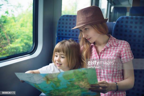 mother and child reading map while travelling by train - passenger train stock photos and pictures