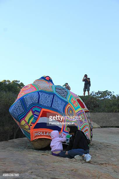 A mother and child relax next to a yarn bomb at Lizard's Mouth Santa Barbara California