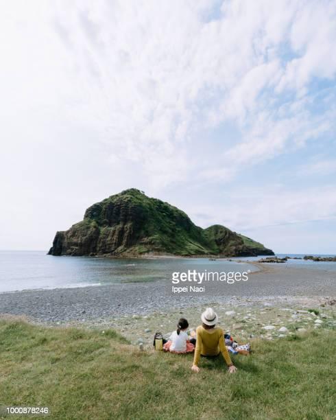 Mother and child relaxing by coast, Sadoshima Island, Niigata, Japan
