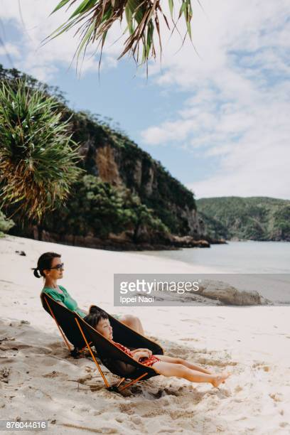 Mother and child relaxing in camping chair on tropical beach, Okinawa, Japan