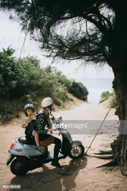 Mother and child riding a scooter to beach