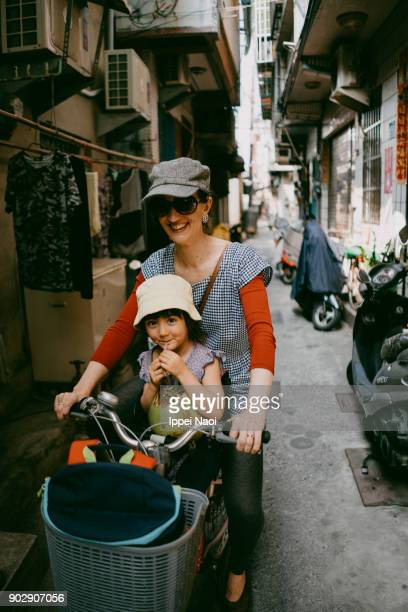 Mother and child riding bicycle through backstreet alley in Taiwan