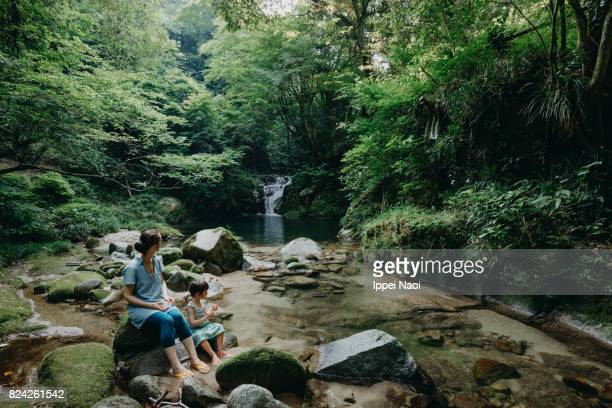 Mother and child sitting by forest river, Japan