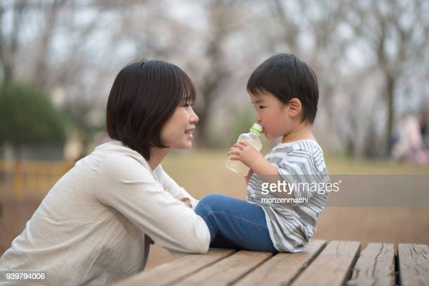 mother and child sitting on bench and talking - childhood stock pictures, royalty-free photos & images
