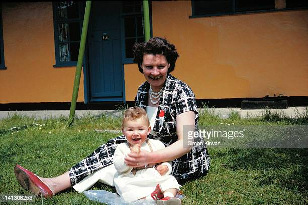 Mother and child sitting on grass