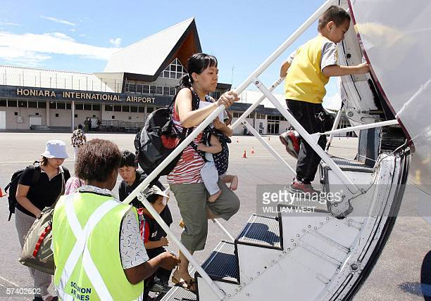 A mother and child some of the nearly 300 Chinese who fear for their safety board their flight as they are flown out of the troubled Solomon Islands...