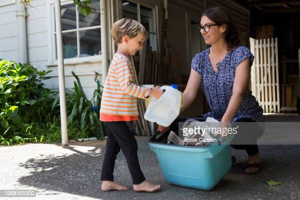 mother and child sorting out the recycling bins - recycling stock pictures, royalty-free photos & images