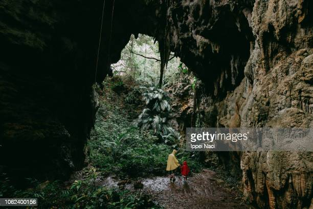Mother and child standing in jungle cave, Okinawa, Japan