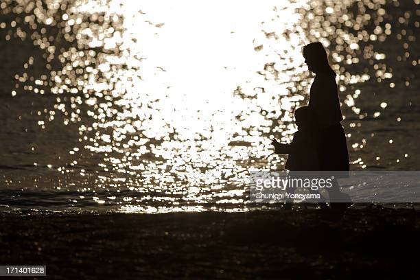 mother and child taking a walk on the beach - zushi kanagawa stock photos and pictures