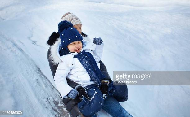 mother and child tobogganing - tobogganing stock pictures, royalty-free photos & images