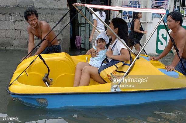 A mother and child use a hired pedal boat to get around in the flooded streets of Malabon north of Manila 13 July 2006 following heavy rains brought...