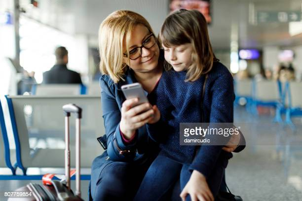 Mother and child using smart phone at airport