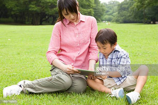 mother and child using tablet PC in the park